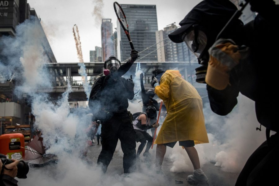 "HONG KONG - AUGUST 25: A protester uses a tennis racquet to hit back tear gas canisters during clashes with police after an anti-government rally in Tsuen Wan district on August 25, 2019 in Hong Kong, China. Pro-democracy protesters have continued rallies on the streets of Hong Kong against a controversial extradition bill since 9 June as the city plunged into crisis after waves of demonstrations and several violent clashes. Hong Kong's Chief Executive Carrie Lam apologized for introducing the bill and declared it ""dead"", however protesters have continued to draw large crowds with demands for Lam's resignation and complete withdrawal of the bill. (Photo by Chris McGrath/Getty Images)"