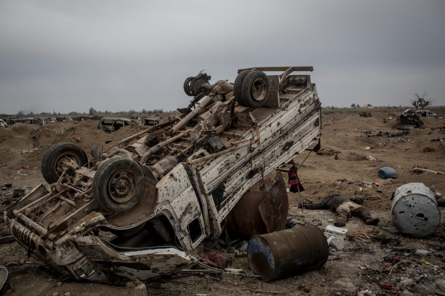 "BAGHOUZ, SYRIA - MARCH 24:  (EDITORS NOTE: Image depicts death)  A body, reported to be an Islamic State fighter is seen next to a destroyed vehicle in the final ISIL encampment on March 24, 2019 in Baghouz, Syria. The Kurdish-led and American-backed Syrian Defense Forces (SDF) declared on Saturday the ""100 percent territorial defeat"" of the so-called Islamic State, also known as ISIS or ISIL. The group once controlled vast areas across Syria and Iraq, a population of up to 12 million, and a ""caliphate"" that drew tens of thousands of foreign nationals to join its ranks.  (Photo by Chris McGrath/Getty Images)"